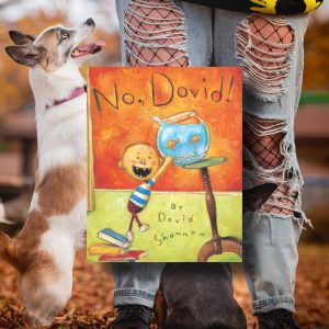 Background is a photo of my dogs jumping on my legs for treats. The book is No, David! by David Shannon